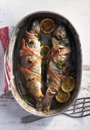 salmo trutta: Trout wrapped in bacon in a roasting tin