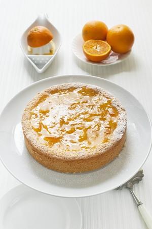 orange cake: orange cake on a cake stand with fresh oranges