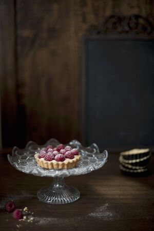cakestand: Small raspberry tart on a glass cake stand