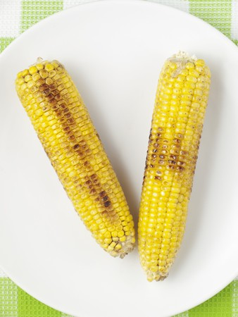 barbie: Two barbecued corn cobs on a plate (view from above)