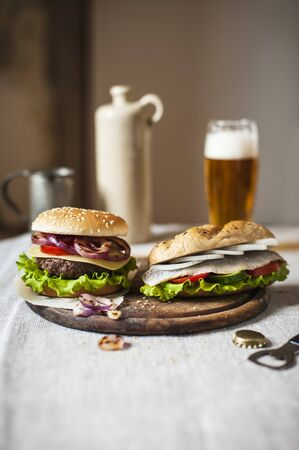 several breads: A beefburger and a herring sandwich on a wooden board LANG_EVOIMAGES