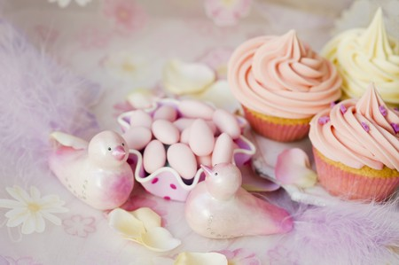 sugared almonds: Cupcakes with buttercream, sugared almonds and pink decorative birds for a wedding LANG_EVOIMAGES