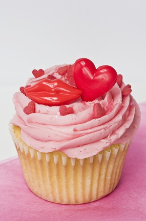 buttercream: A cupcake topped with pink buttercream icing, red lips and hearts