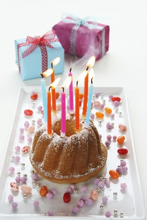 8 years birthday: A birthday cake with lit candles being blown out, and wrapped presents LANG_EVOIMAGES