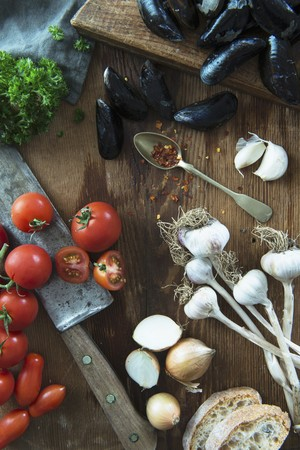 petroselinum sativum: A still life featuring mussels, garlic, onions, tomatoes and parsley