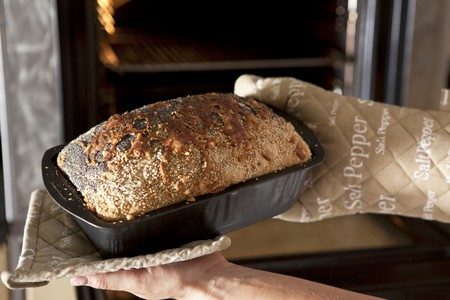 multi grain sandwich: Hands holding a loaf tin with freshly baked wholemeal bread