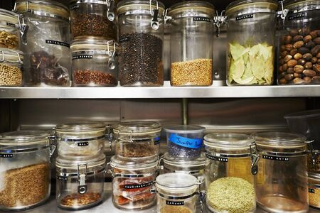 Assorted Dried Ingredients in Storage Containers on Metal Shelves