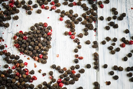 scattered in heart shaped: Red and black peppercorns in the shape of a heart