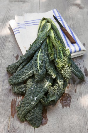 washed out: Washed cavolo nero (organic) with a linen cloth and a knife on a wooden table outdoors