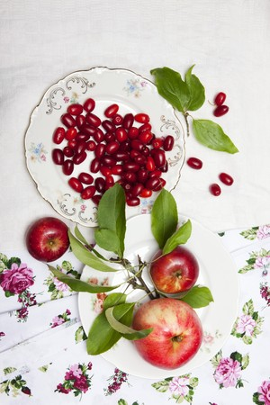 windfalls: Cornel cherries and apples with leaves on a plate