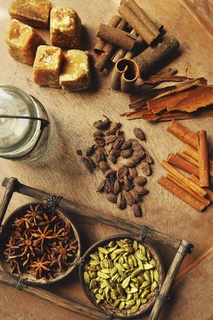 'cinnamon bark': Assorted spices on a wooden table (cinnamon bark, cinnamon sticks, star anise, cardamom and palm sugar) LANG_EVOIMAGES