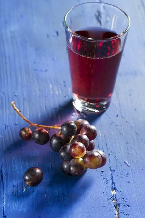 and grape juice: Red wine grapes and grape juice on a bllue wooden tabletop LANG_EVOIMAGES