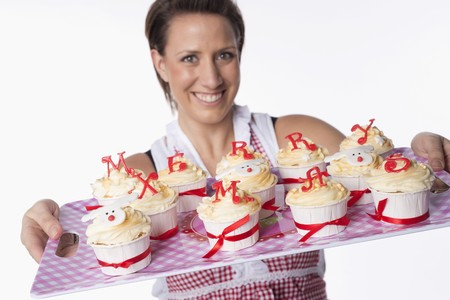 solo  christmas: A woman holding a tray of cupcakes topped with letters reading Merry Xmas