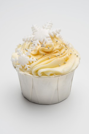 solo  christmas: A cupcake decorated with yellow icing, silver balls and snowflakes LANG_EVOIMAGES