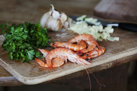petroselinum sativum: Whole king prawns, parsley and garlic on a chopping board LANG_EVOIMAGES