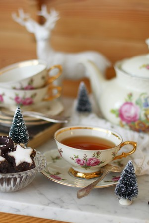 teaset: A cup of tea with a rose pattern and Christmas biscuits