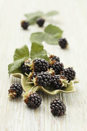 brambleberries: Fresh blackberries with leaves in a bowl and to one side LANG_EVOIMAGES