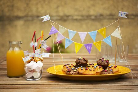 childrens food: Muffins with chocolate beans, marshmallows and orange juice for a childs birthday