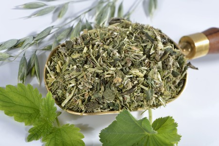 alchemilla vulgaris: A mixture of herbs on a brass scoop (oats, stinging nettle, ladys mantle) LANG_EVOIMAGES