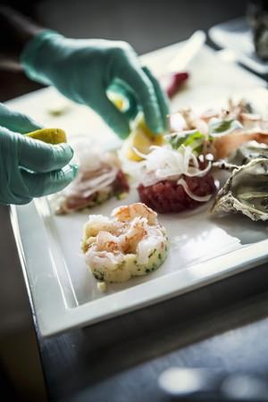 plato de pescado: Un chef de la organizaci�n de un plato de pescado en un plato de porcelana blanca LANG_EVOIMAGES