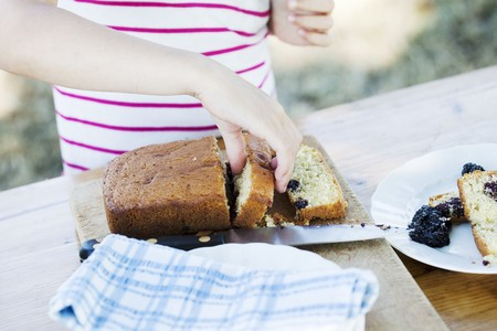 provenance: A girl picking up a slice of blackberry cake