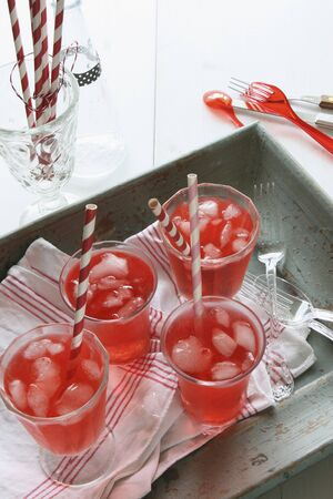 soda pops: Red lemonade with ice cubes and straws on a wooden tray