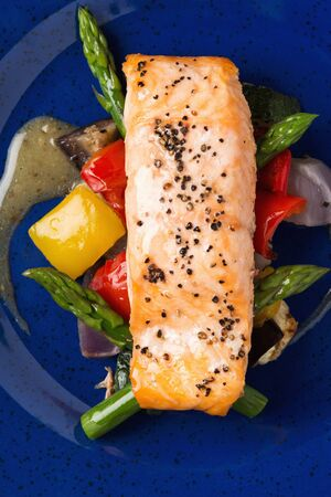 A salmon fillet on a bed of asparagus and peppers