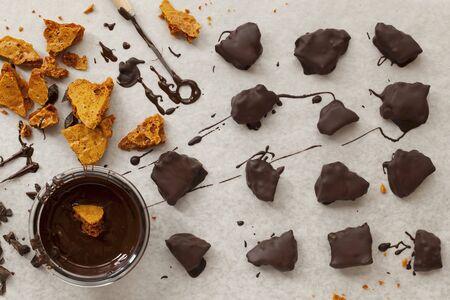 chocolate derretido: Los pedazos de panal que se sumergen en el chocolate derretido oscuro