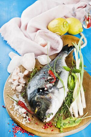 sea bream: Sea bream on a wooden board with Himalayan salt and various herbs LANG_EVOIMAGES