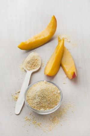 freeze dried: Mango de frutas en polvo en un recipiente de vidrio y en una cuchara