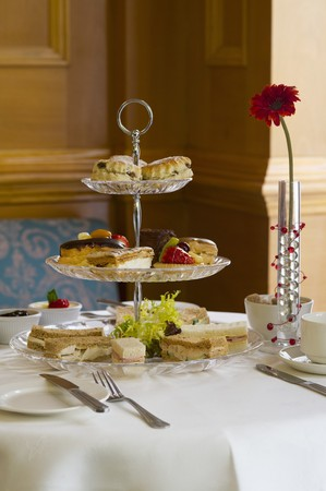 uk cuisine: Biscuits, sweet pastries and sandwiches on a cake stand for high tea (England)