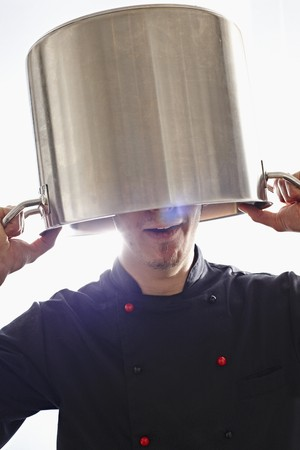 30 to 35 year olds: A chef holding a pot over his head