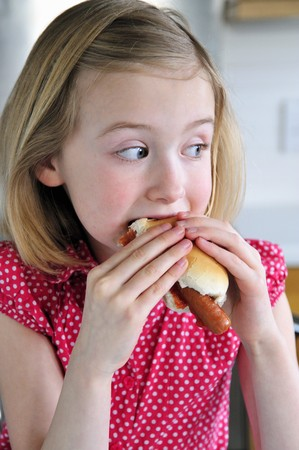 10 to 12 year olds: A little girl eating a hot dog