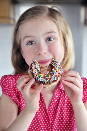 10 to 12 year olds: A little girl eating a doughnut with sugar sprinkles