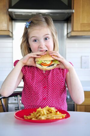 10 to 12 year olds: A little girl eating a hamburger and fries