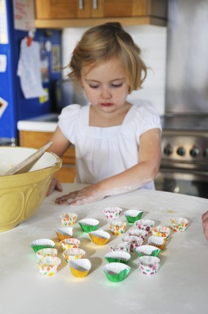 being the case: A little girl in a kitchen helping with baking