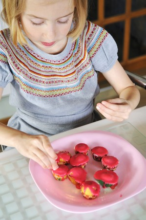 10 to 12 year olds: A girl decorating mini muffins in a kitchen