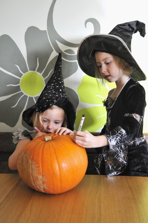 10 to 12 year olds: Two girls in Halloween costumes preparing a pumpkin for carving