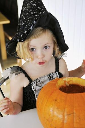 enquiring: A little girl in a Halloween costume with a pumpkin