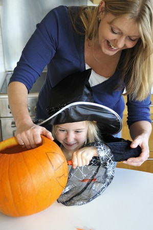 35 to 40 year olds: A mother and daughter preparing a Halloween pumpkin for carving