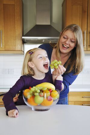 35 to 40 year olds: A mother feeding her daughter grapes in the kitchen LANG_EVOIMAGES