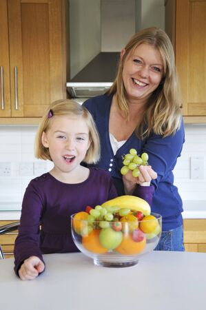 35 to 40 year olds: A mother and daughter in the kitchen with a bowl of fruit LANG_EVOIMAGES