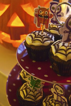 childs birthday party: Spooky Halloween cupcakes decorated spider webs on a cake stand