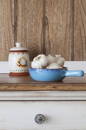 Garlic bulbs in a blue ceramic bowl