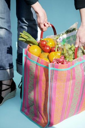 provenance: A woman holding a shopping bag of fresh fruit and vegetables LANG_EVOIMAGES