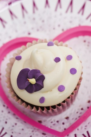 doiley: A cupcake decorated with a purple sugar flower on a paper doily