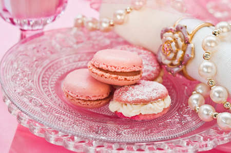 glass topped: Pink macaroons on a glass plate with a pearl necklace and a napkin