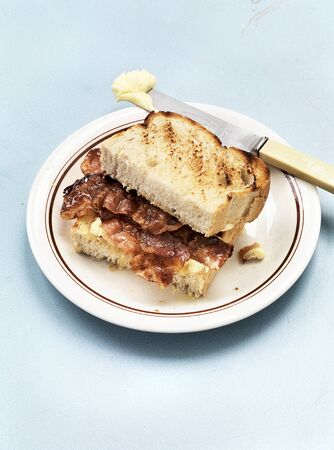 toasted sandwich: A toasted sandwich with bacon and butter