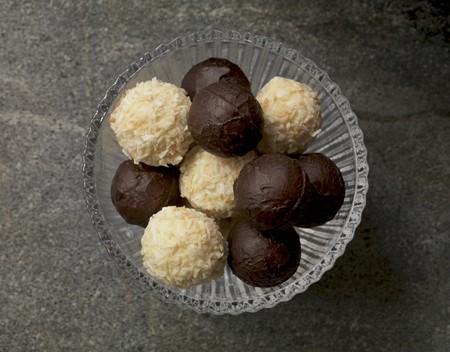 trufas de chocolate: Trufas de chocolate blanco y oscuro en un recipiente de vidrio