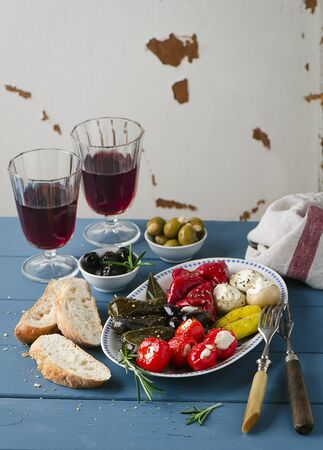 appetiser: An appetiser platter with stuffed vine leaves and vegetables, white bread and red wine
